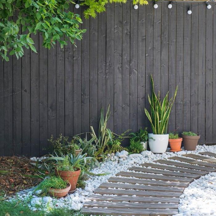 chemin de jardin en galets blans et plaches de bois avec bordure de pierre et de pots de flers, idee deco jardin cocooning cosy