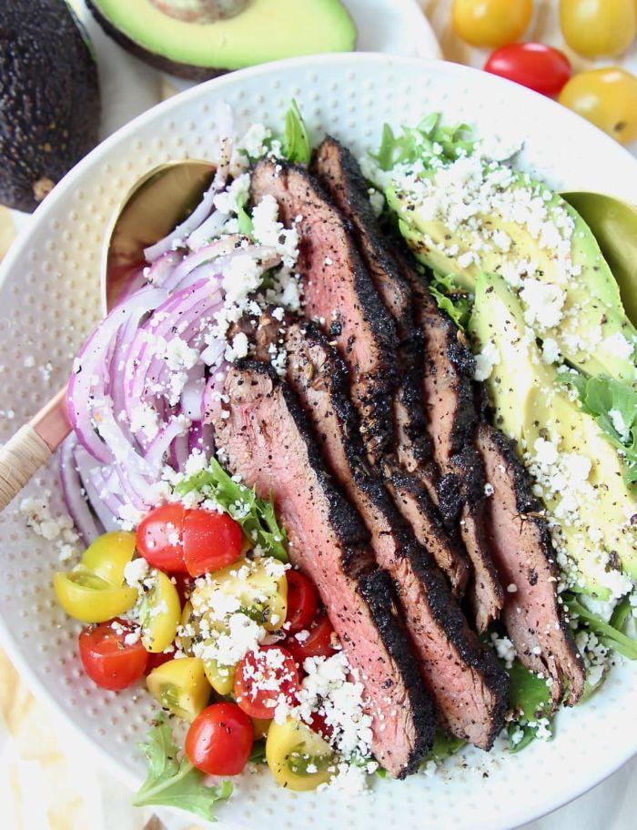 idée grillade barbecue boeuf grillé avec salade tomates oignons et feta et des tranches d avocat