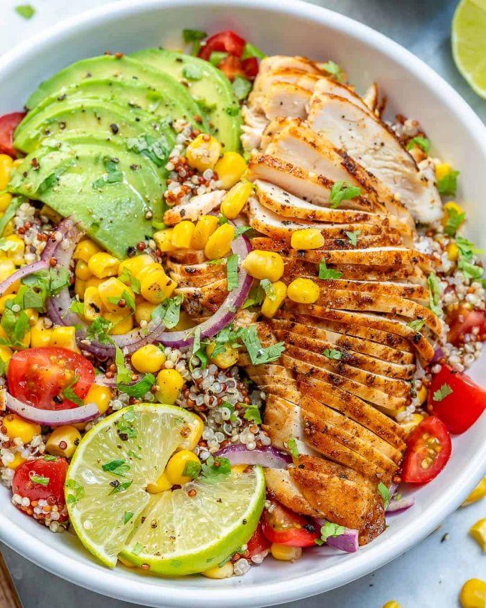 exemple de salade composée originale de quinoa, mais, tomates, avocat, persil et autres legumes servie avec du poulet