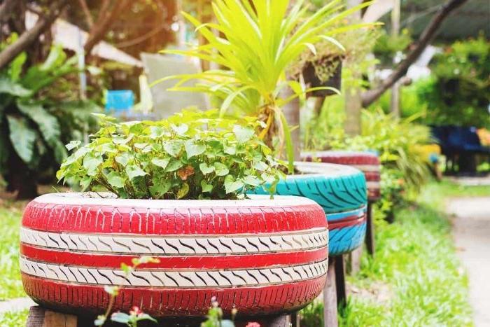 fabriquer une jardiniere dans un pneu recyclé fleuri sur pieds de bois, idee deco a faire soi meme recup pour la bordure de jardin