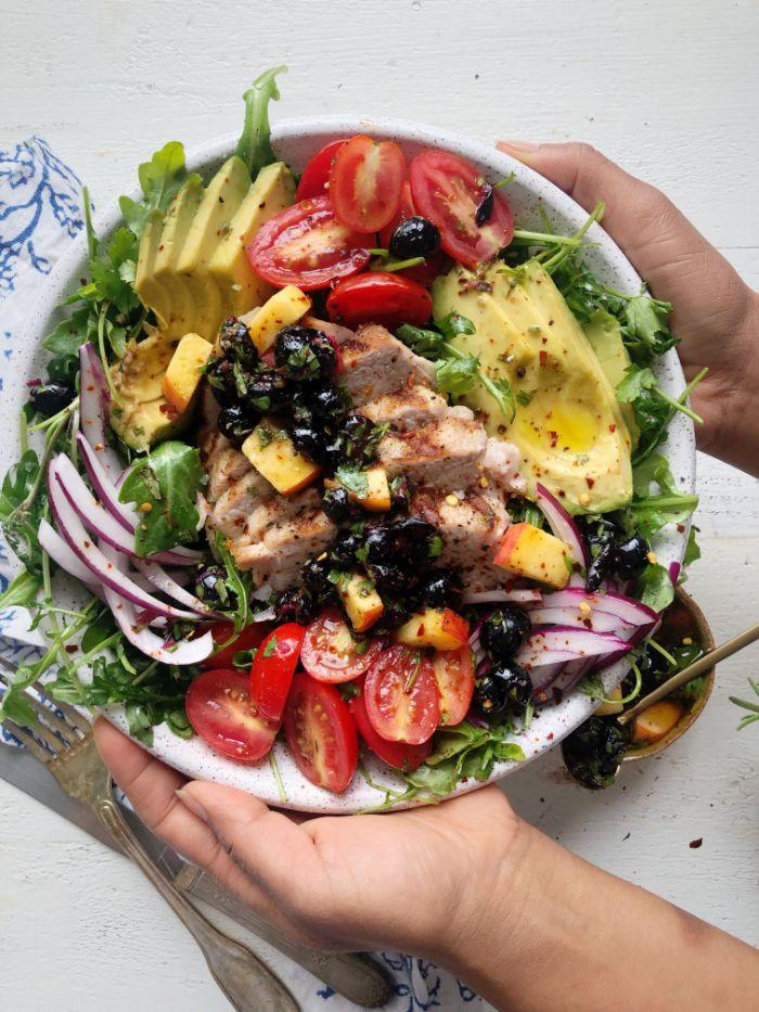 recette poke bol salade cmposée originale de tomates cerise, olives, oignons, avocat, roquette avec du blanc de poulet grillé