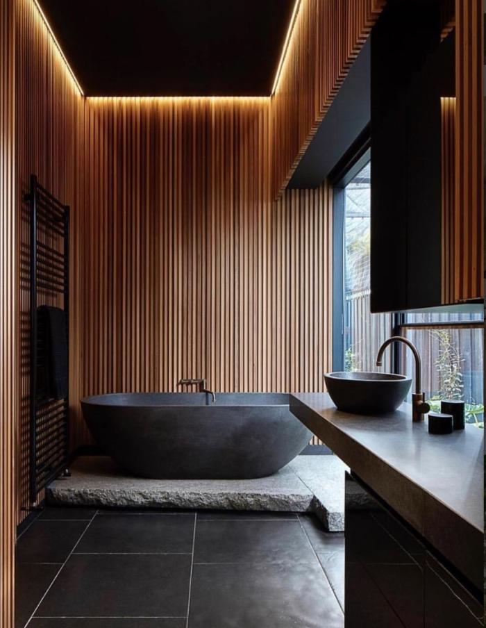 idée déco salle de bain relax, design salle de bain aux murs en bois avec sol en gris anthracite, modèle de baignoire gris foncé
