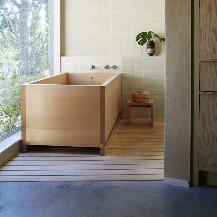 modèle de baignoire japonaise bois installée sur un tapis en bois clair, décoration salle de bain de style zen avec plantes et bois