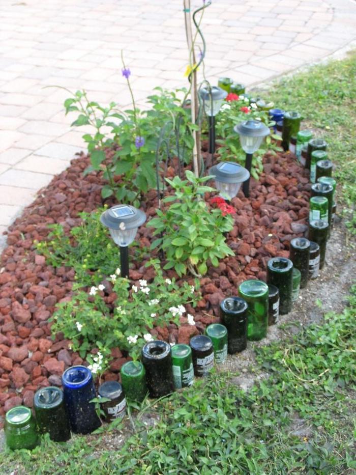 petite rocaille fleurie bordée de bouteilles de vin en verre plantée à l envers, idee deco jardin recup originale