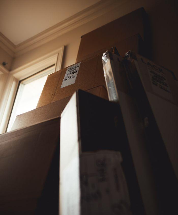 pile de cartons de déménagement dans une chambre, déménagement particulier formalités et démarches