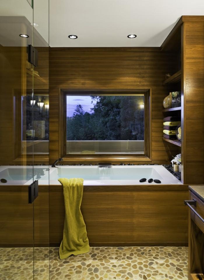 aménagement petite salle de bain avec baignoire, design salle de bain aux murs en bois avec sol en cailloux et accents métal