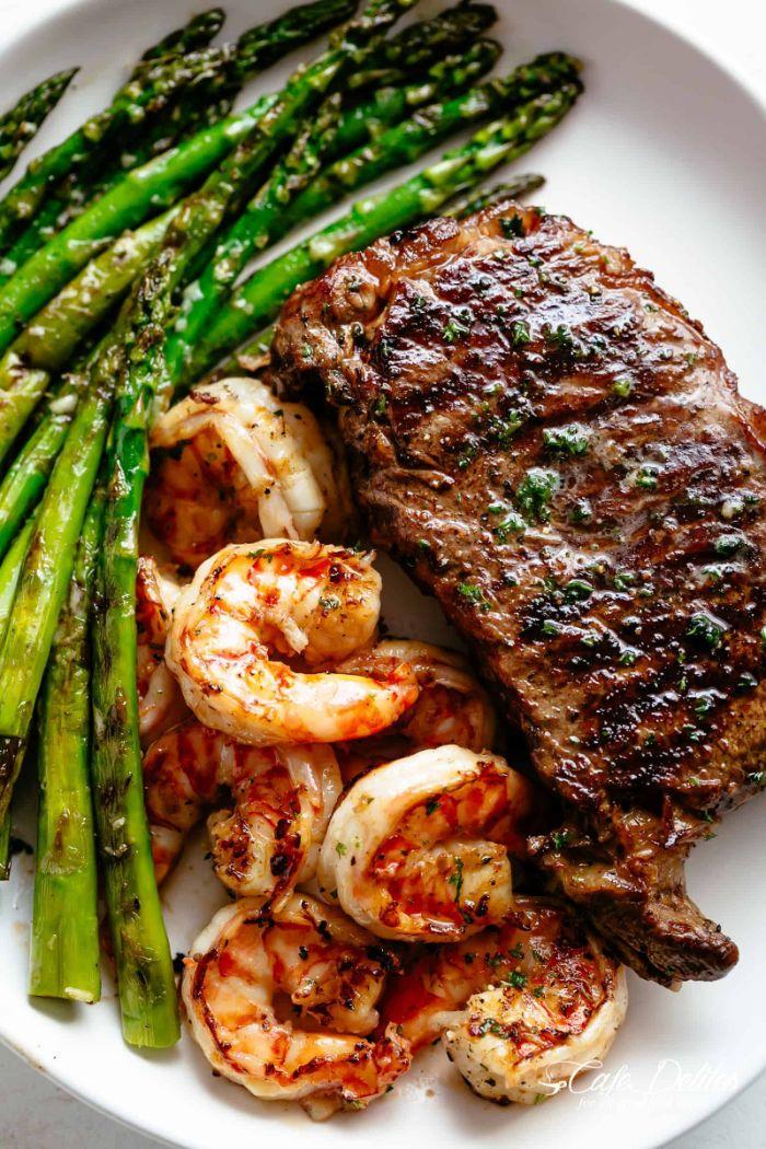 asperges grillées comme accompagnement grillade de crevettes et bifteck de boeud dans assiette blanche
