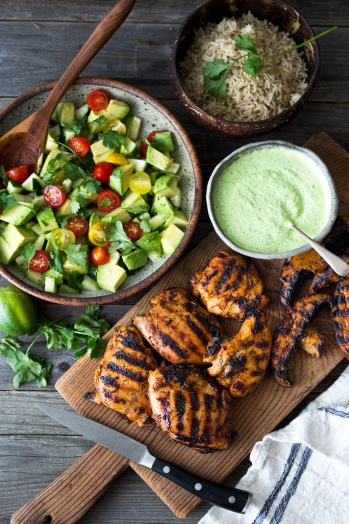 cuissnes de poulet grillées servis avec idée accompagnement barbecue de salade avocat et tomates cerise, riz et sauce yaourt