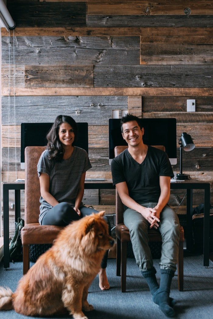 adorable couple avec son chien dans une maison en bois intérieur mur habillé en bois grands sourires mignon chien