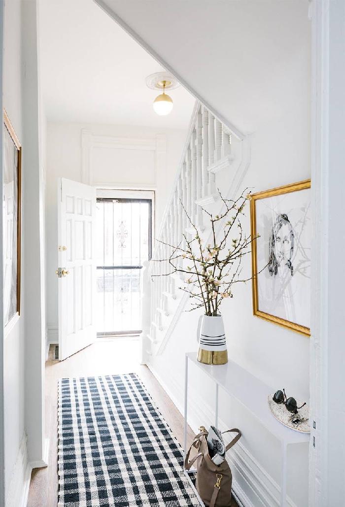 aménagement entrée étroit tapis blanc et bleu motifs carreaux cadre peinture doré photo blanc et noir déco sous escalier moderne