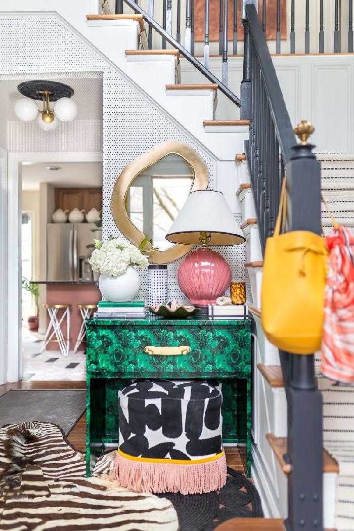 aménagement entrée maison style éclectique escalier blanc et or miroir cadre or lampe rose coquillage tabouret blanc et noir franges roses