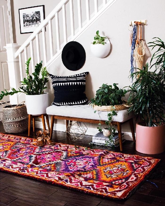 aménagement entrée maison tapis multicolore rectangulaire panier tressé banquette blanc et bois coussin noir motifs géométriques