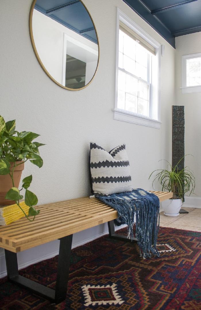 banquette bois pieds métal miroir rond cadre or aménagement entrée maison interieur plante verte pot fleur terre cuite coussin blanc et gris