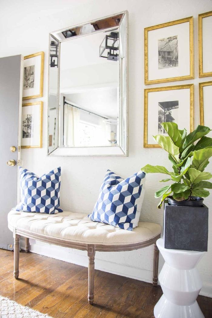 banquette coussin décoratif blanc et bleu pot fleur aspect béton mur de cadres dorés aménagement entrée maison interieur miroir