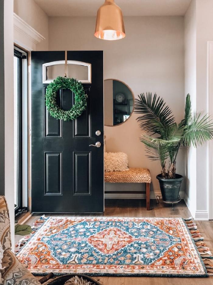 banquette entrée bois et paille palmier d intérieur miroir rond cadre or tapis orange et bleu franges revêtement sol parquet bois