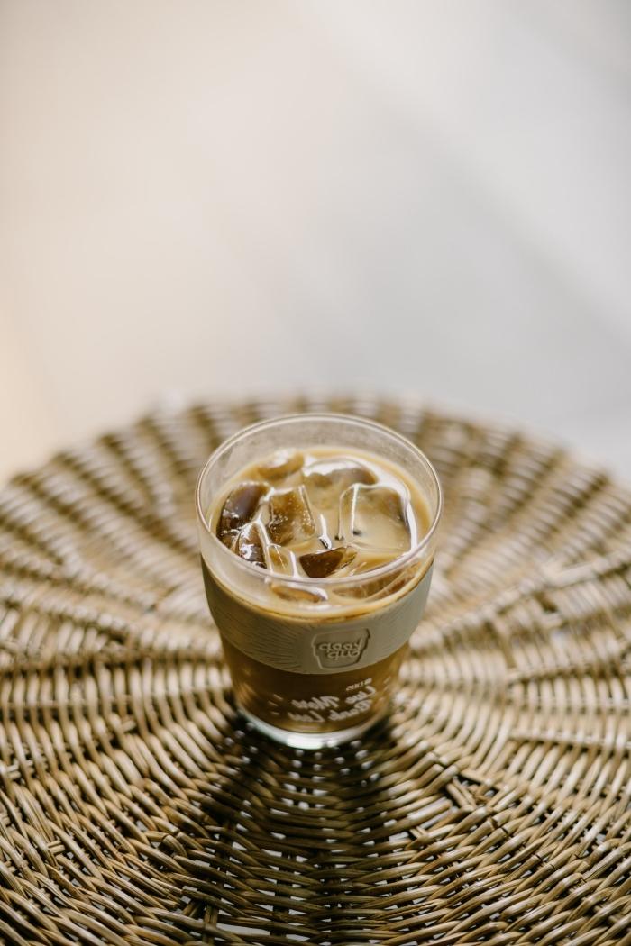 idée comment servir une boisson frappée sur un sous-verre-exotique tressé, verre rempli de café au lait et glaçons