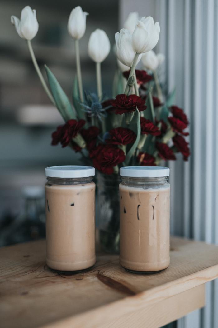 comment faire un café frappé facile, pots en verre remplis de café froid sur un îlot en bois clair décoré de bouquet de fleurs