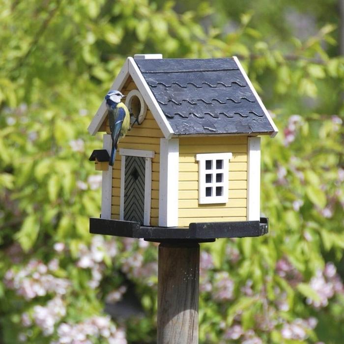modèle de cabane pour oiseaux avec façade jaune et fenêtre blanche à toit gris foncé, maison sur pied pour petits oiseaux