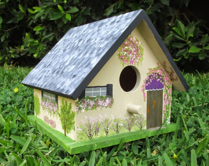 modèle de petite cabane à oiseaux décorée avec peintures sous forme de fenêtre et portes avec véranda en peinture verte