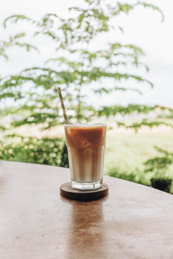 recette café glacé facile à réaliser maison, verre rempli de lait et de glaçons avec mousse au café instantané et sucre