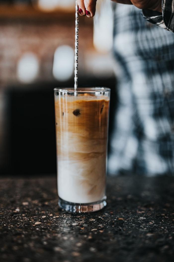boisson frappée facile à préparer à la maison, verre rempli de boisson au café instantané et lait avec glaçons sur une surface noire