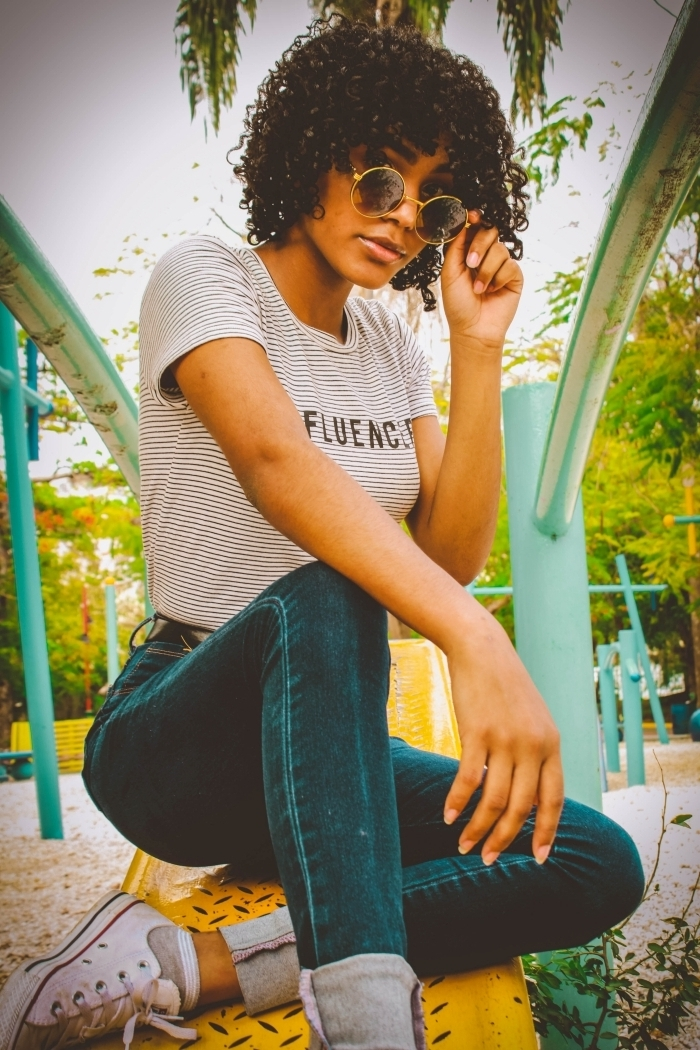 cheveux crépus coupe de cheveux femme jeans foncés sneakers blanches modele de coiffure courte t shirt blanc rayures lunettes soleil tendance