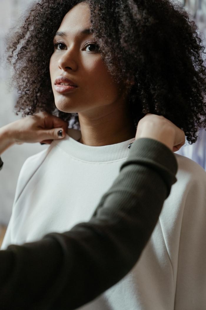 cheveux crépus noirs coupe courte feminine maquillage naturel mascara noir fards a paupières nude blouse blanche