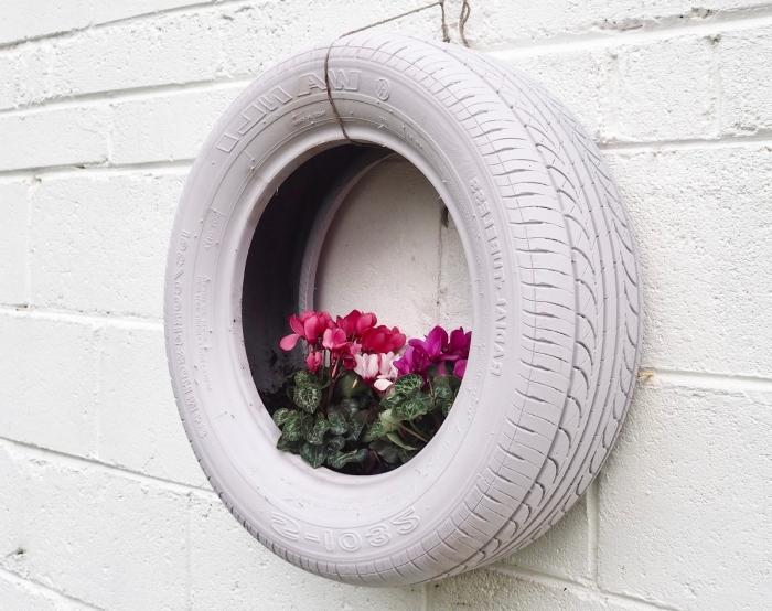 exemple de décoration murale pour jardin avec objet recyclé, modèle de jardinière DIY en pneu recyclé accroché au mur
