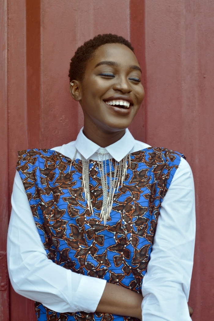 coupe cheveux très court femme chemise blanche collier frange or robe bleue motifs marron piercing oreille fards à paupières bleus