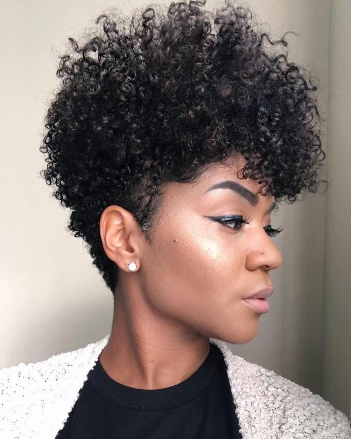 coupe courte feminine cheveux noirs volume coiffure cheveux crépus avec volute sur le haut de la tête maquillage eye liner noir boucles d oreilles