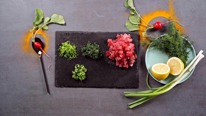 hacher lees herbes fraiches et préparer le thon pour faire tartare thon rouge, idée entrée légère