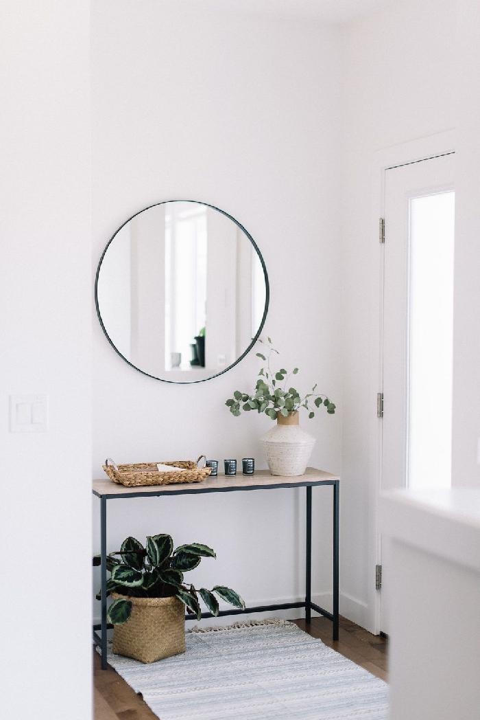 déco entrée maison style minimaliste intérieur déco scandinave couloir blanc meubles métal noirci panier tressé tapis franges miroir rond
