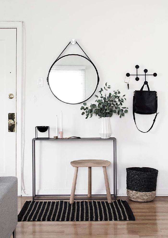 décoration entrée appartement design scandinave style minimaliste miroir rond noir vase origami blanc tabouret bois clair panier tressé beige et noir