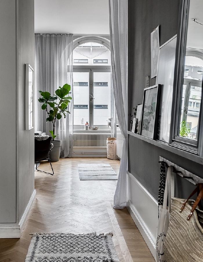 décoration entrée appartement style parisien rideaux longs blancs revêtement de sol parquet bois plante verte cadres miroir tapis franges