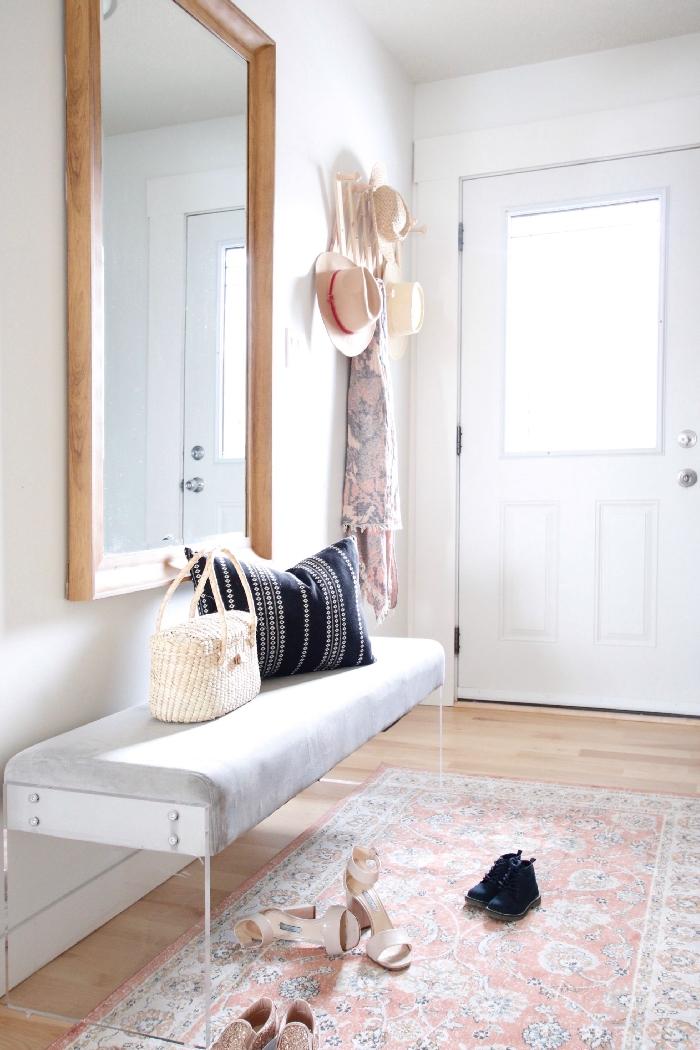 deco hall d entrée couleurs neutres miroir rectangulaire cadre bois banquette velours blanc et gris clair tapis beige chaussures talons