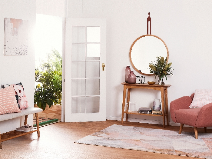 design intérieur tendance aménagement entrée avec meubles en bois peinture couloir blanc accents en rose fauteuil miroir rond