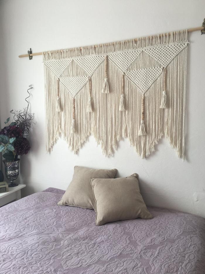 design petite chambre bohème aux murs blancs avec meubles en bois blanc table de chevet tete de lit macrame cotton beige bâton bois tassels