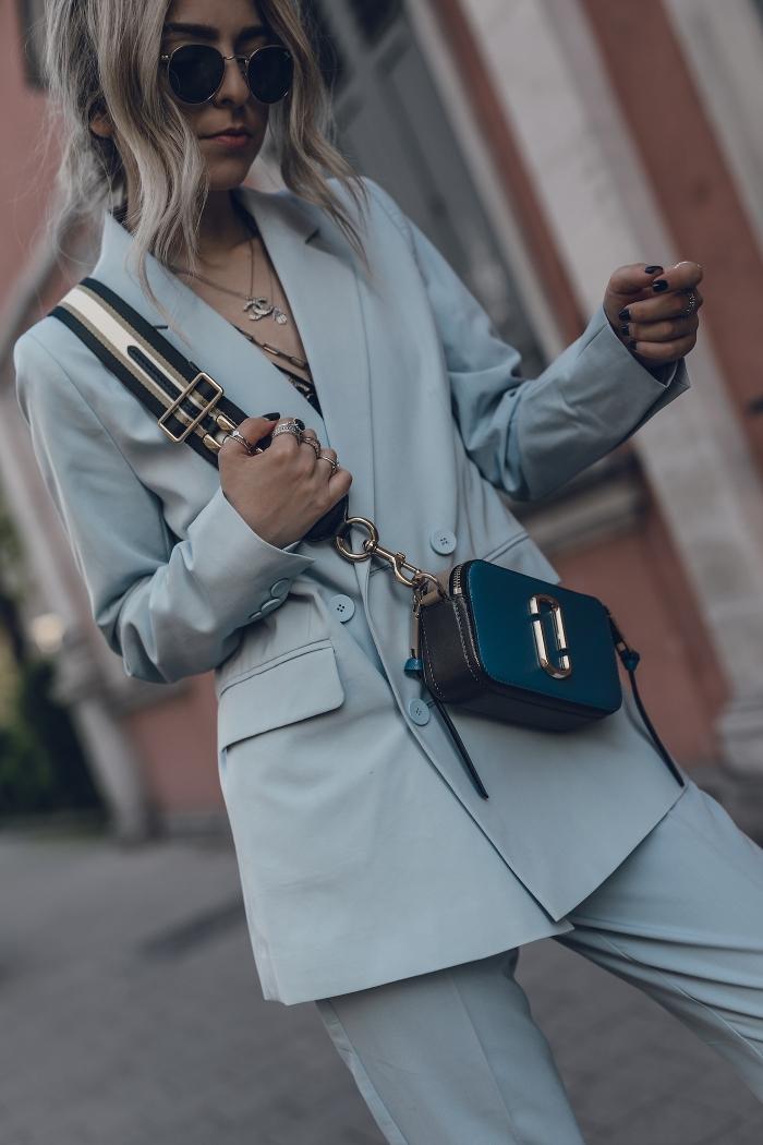 idée de tenue smart casual pour femme d'affaires, exemple de pantalon tailleur femme de couleur gris clair à combiner avec accessoires noirs