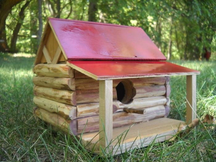 assemblage de morceaux sous forme de cabane oiseaux originale avec toit rouge et petite terrasse en bois