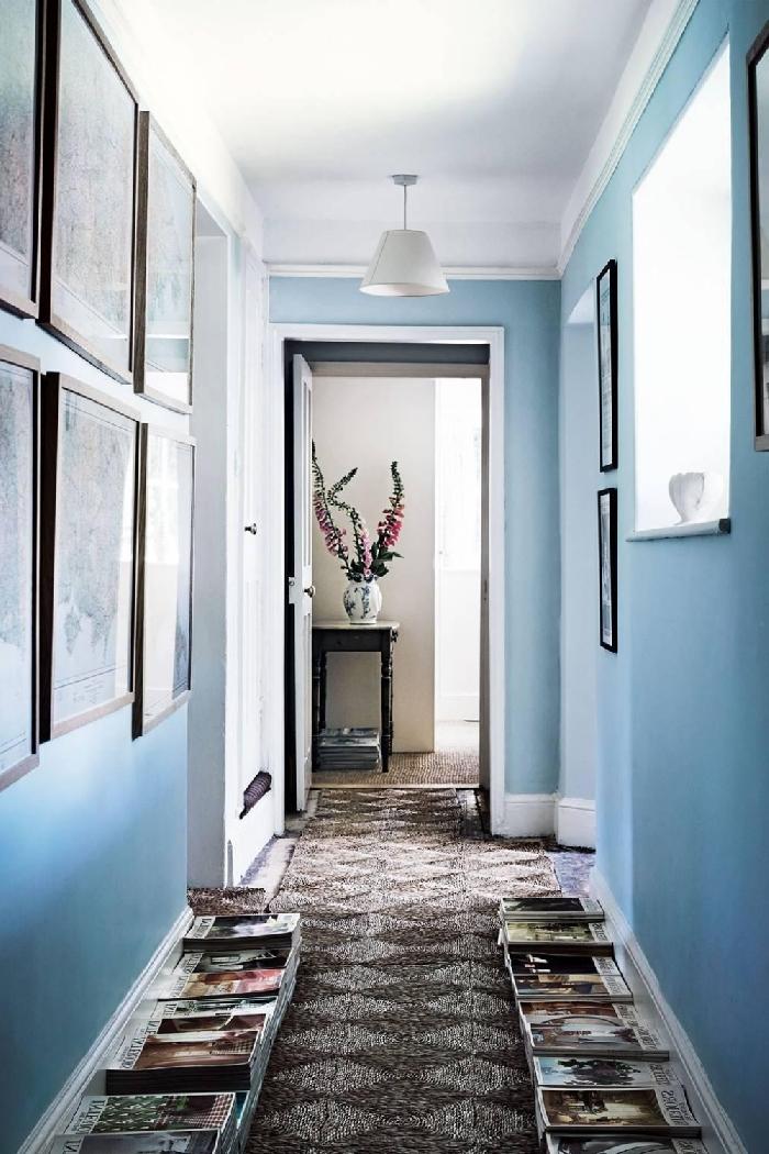 idée déco couloir peinture tendance mur bleu mur de cadres photos bois livres par terre tapis gris motifs géométriques porte noire