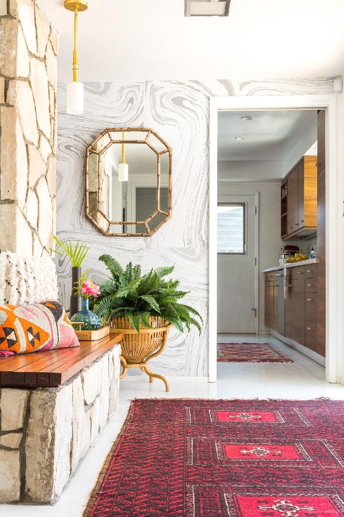 idée déco entrée maison moderne revêtement mural papier peint aspect marbre tapis rouge mur pierre miroir or banquette bois