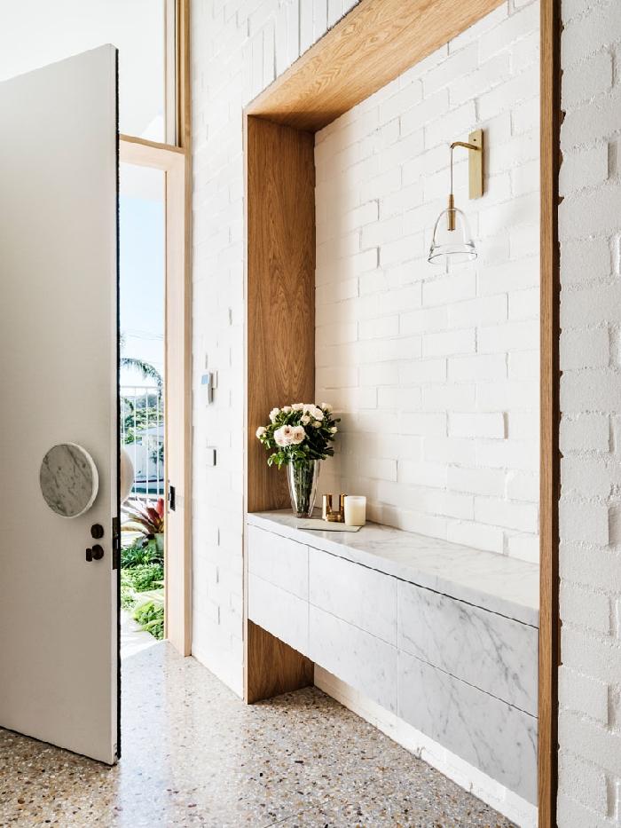 idée déco entrée maison revêtement mural briques blanches accents bois vase verre applique murale porte blanche meuble marbre