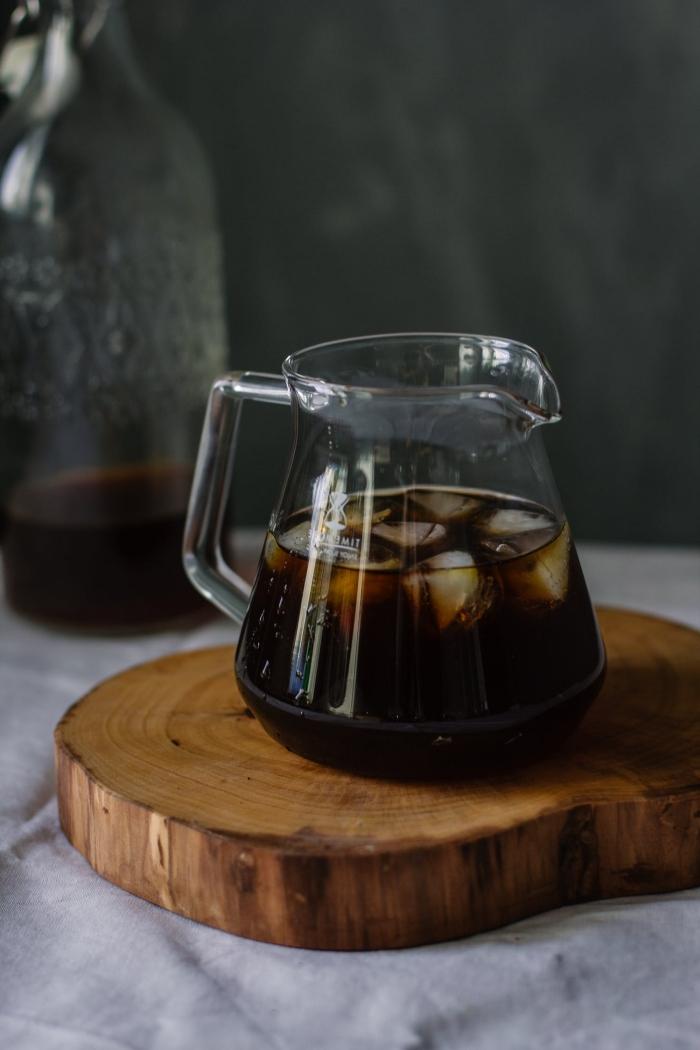 comment préparer un café glacé nespresso, recette de café noir froid pour l'été, verre de café noir avec glaçons sur tranche de bois