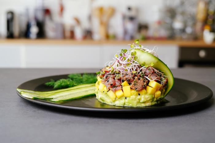 tartare avocat er saumon avec une couche de mangue, graines de sésame noirs et décoration de concombre et pousses