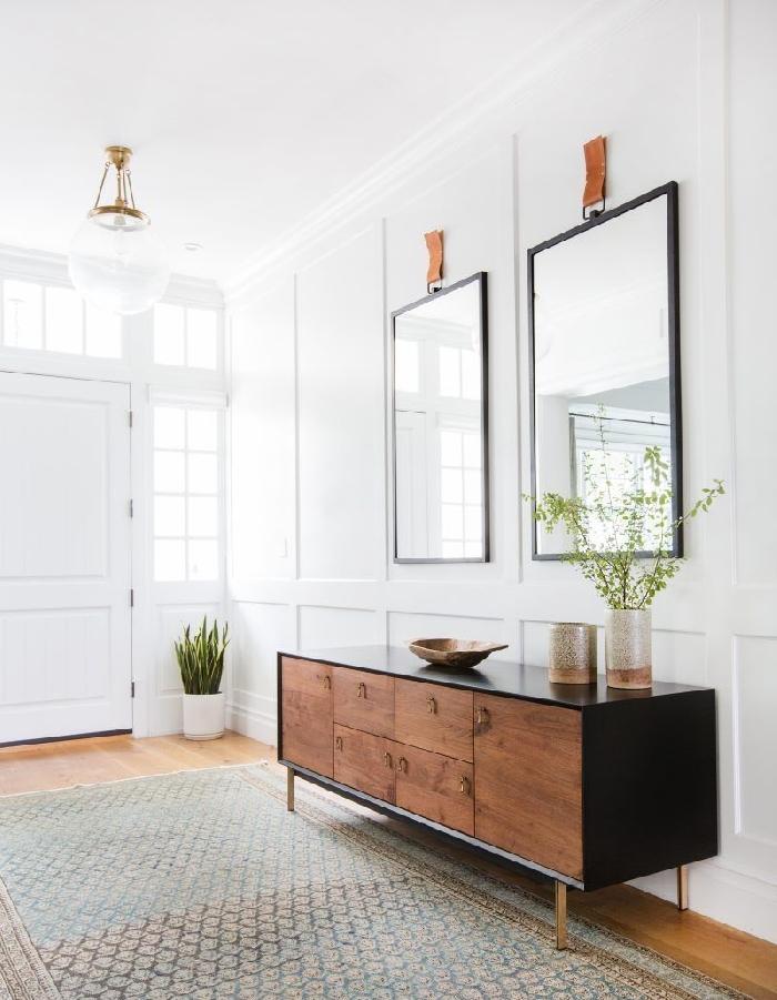 idee deco maison moderne miroir rectangulaire noir lampe boule or verre meuble noir et marron tapis motifs géométriques plantes vertes