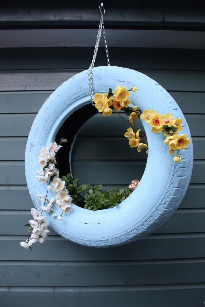 idée de décoration extérieure facile à faire avec objet recyclé, modèle de jardinière en pneu peint en blanc avec chaîne métal