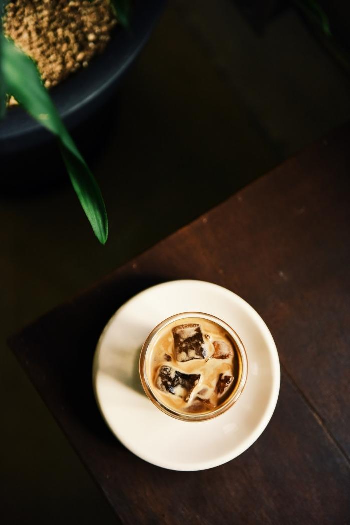 comment préparer un café glacé maison facile, verre rempli de café au lait refroidi avec glaçons sur une assiette ronde
