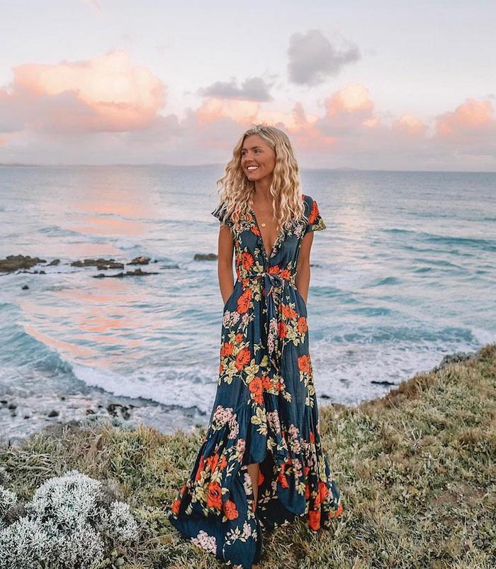 longue robe avec manche courte et decolette en v femme blonde cheveux ondulés souriante vue de l ocean au coucher de soleil robe longue femme ete inspiration robe fleurie femme tenue tendance