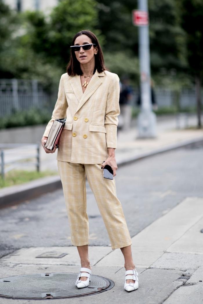 modèle de pantalon tailleur femme de couleur jaune et blanc accessoirisé avec lunettes de soleil et sac à main tendance