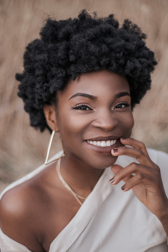 maquillage avec eye liner noir fards à paupièrs dorés coiffure africaine femme couleur de cheveux noirs cheveux crépus boucles d oreilles pendents collier